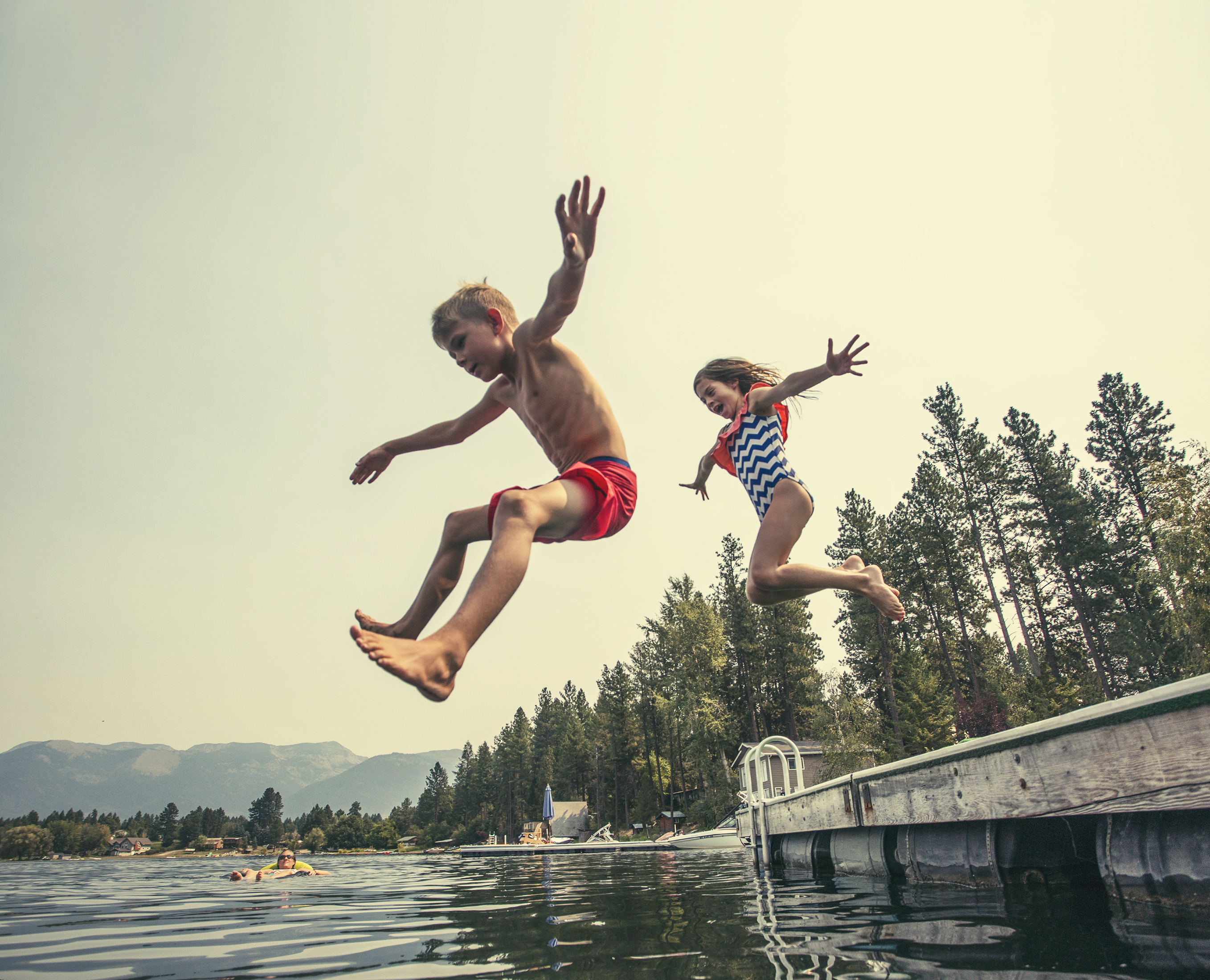 boy and girl jump into lake from dock