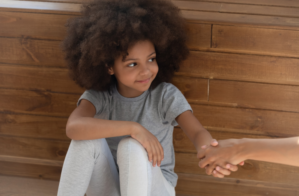 Smiling child holding hands with caring adult